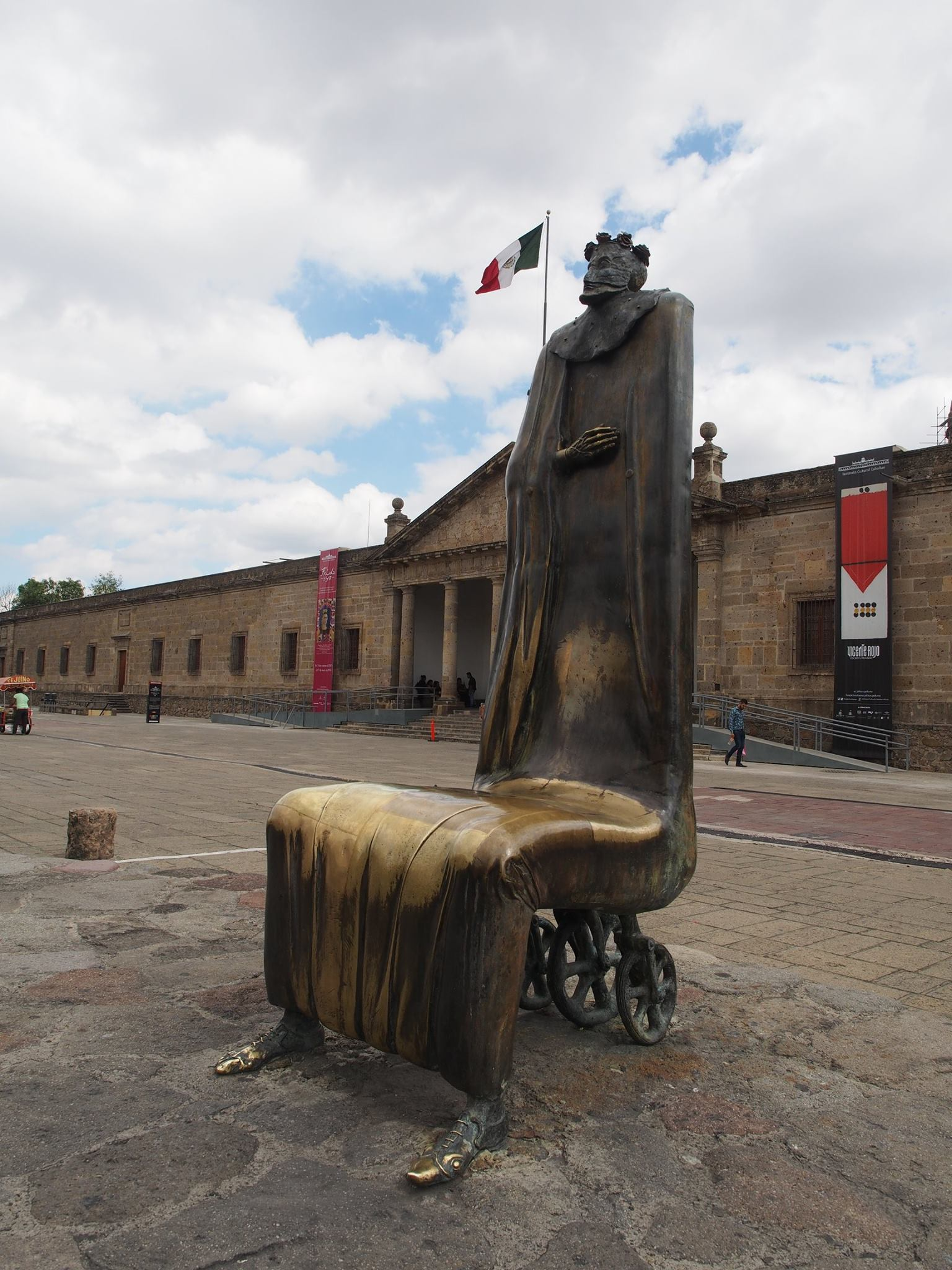 chair sculpture in front of mexican flag and building